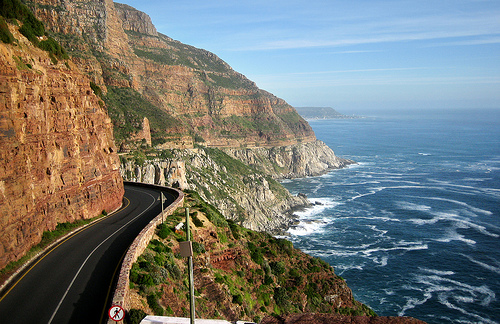 Road winding around a mountain pass with the ocean beside it