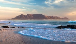 white water waves break onto sand with blue skies over table mountain