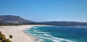 Sandy beach, waves breaking onto beach, mountain in background
