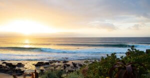Sun setting while surfers catch waves in Jeffreys Bay