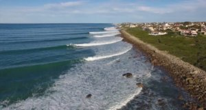 trees, rocks, waves breaking along a point